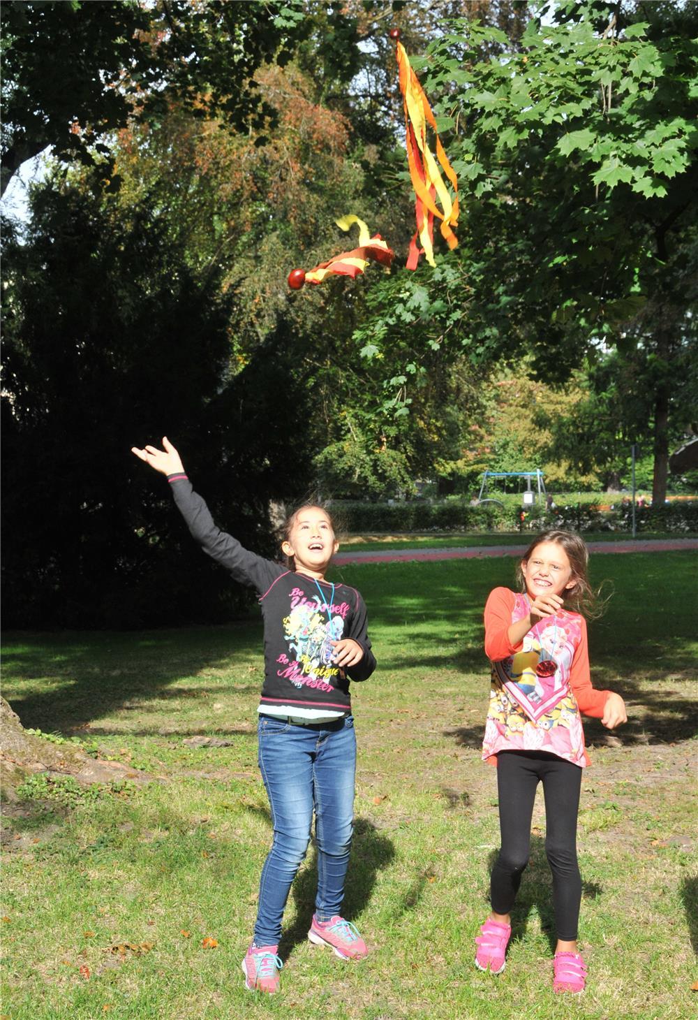 zwei Kinder werfen Kastanien, an denen bunte Bänder hängen, in die Luft