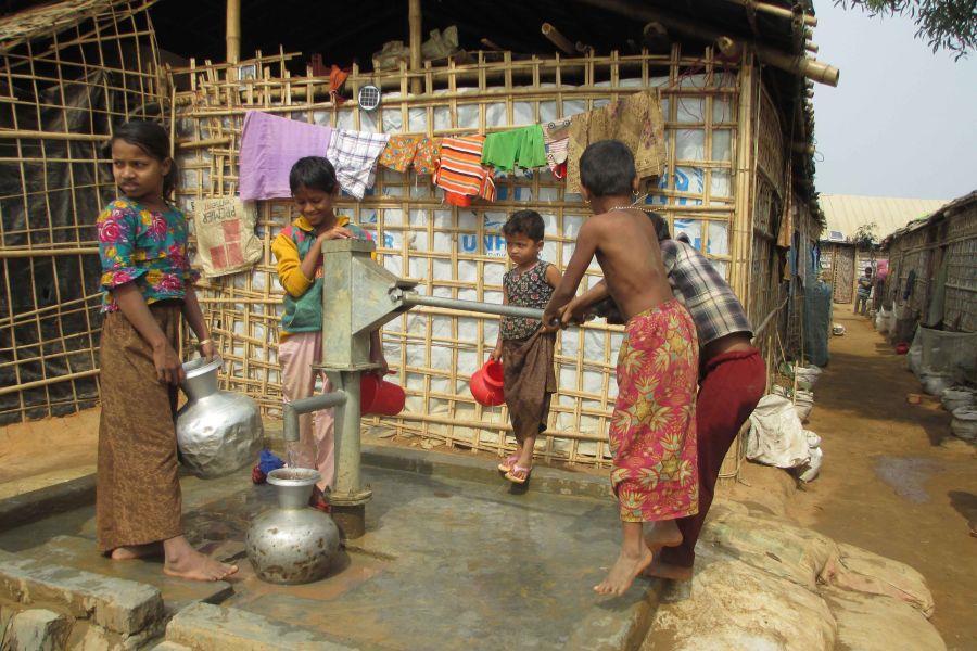 Kinder an einem Pumpbrunnen im Caritas Modelldorf in Bangladesch
