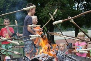 Kinder mit Stockbrot an Lagerfeuer