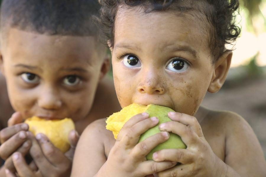zwei Kinder essen Mango (Foto: Caritas Internationalis)