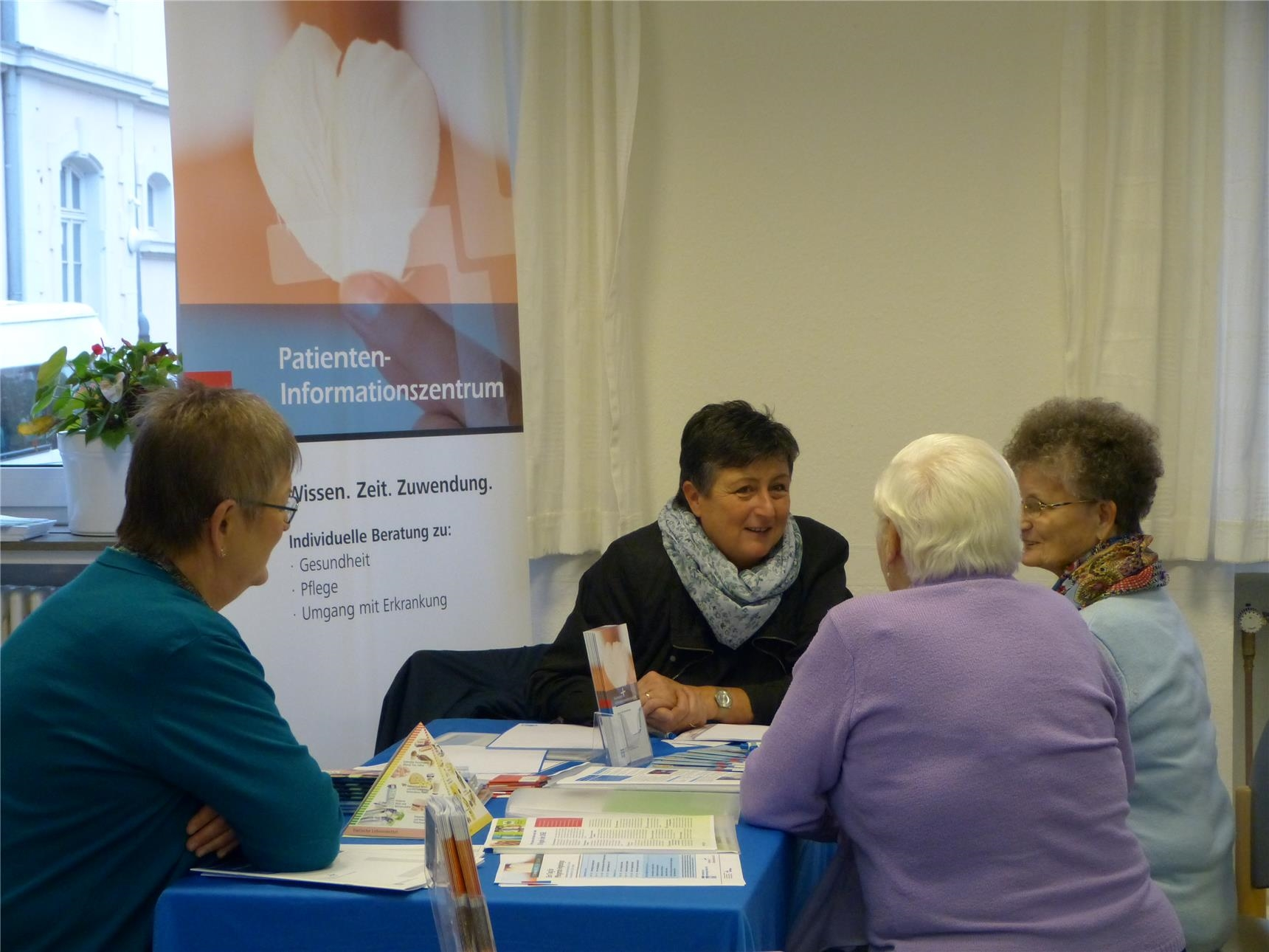 "vier Frauen an einem Tisch, im Hintergrund ein Banner mit der Aufschrift ""Patienten-Informationszentrum"". (Quartiersmanagement Trier-West/Caritasverband Trier e. V.)"