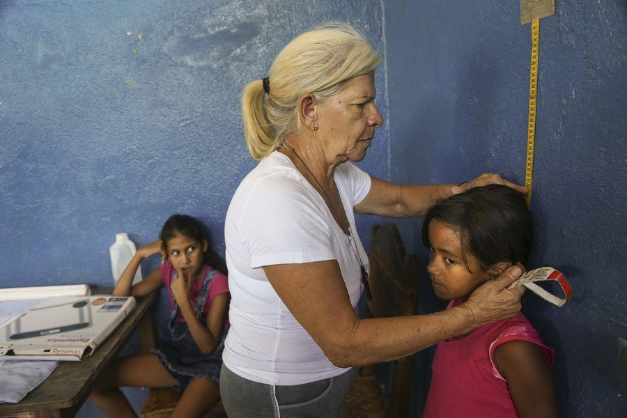 Frau misst ein Kind (Foto: Caritas Internationalis)